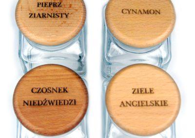 Grawerowane nazwy przypraw na drewnianych wieczkach pojemników