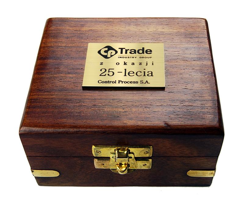 Złota tabliczka z grawerem naklejona na drewniane pudełko